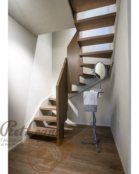 scala in rovere tinto con scalini sospesi e fianchi a finto muro in legno di toulipier